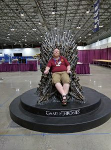 Brian Nisbet sitting in a replica of the iron throne from the TV show Game of Thrones, with a large convention venue in the background