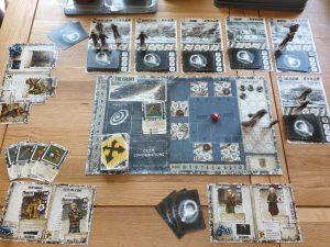 A setup of 'Dead of Winter' with the board centred. The board includes a count of the game's rounds, a floorplan of the colony with a red dice in the middle, and miniature character cut-outs. Around the board are various character and item cards.