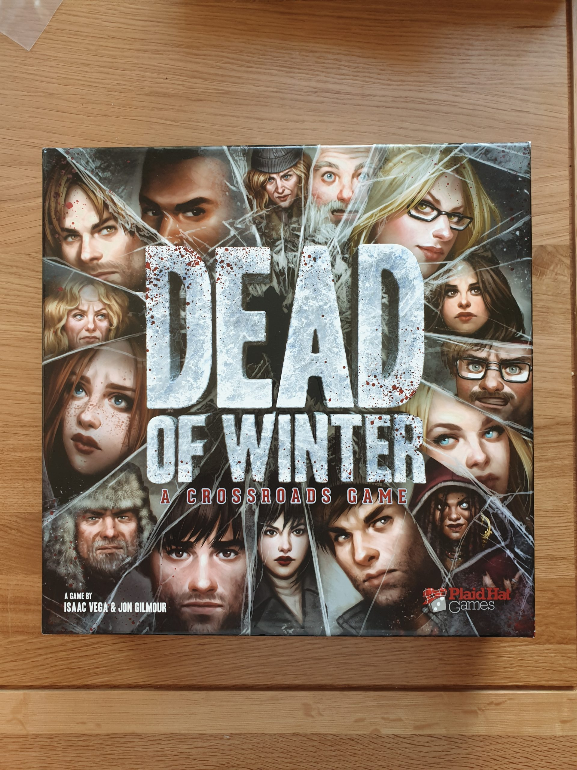 The front of the game's box, with 'Dead of Winter' centred in large silvery letters and flecked with spatters of red. In a circle around the edges of the box are 15 characters, divided by lines of broken ice.