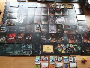 The 'This War of Mine' board, featuring a large darkly coloured board with various cards, character pieces, prompts, and tokens.