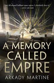 The image shows the cover of A Memory Called Empire by Arkady Martine. The image is a wide view of a throne room with steps leading up to a throne. The throne is styled to look like the rays of a radiant run. On the throne a person in a white robe sits. Another person stands at the top of the throne facing it. The bottom half of the image is overlaid by the title and authors name in a gunmetal golden font.