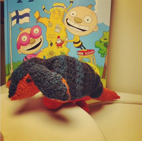Crochet armadillo with a red body and dark blue armour, looking to the left. Photographed in front of a Finnish children's book.
