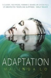 The image shows the cover of Malinda Lo's novel 'Adaptation'. The cover is split into 1 third white (this is the top) and 2 thirds green. In the white third a face with pale skin and wet slicked back hair rises up out of the green third. The green thrid is made too look like rippling water on which the face is reflected.