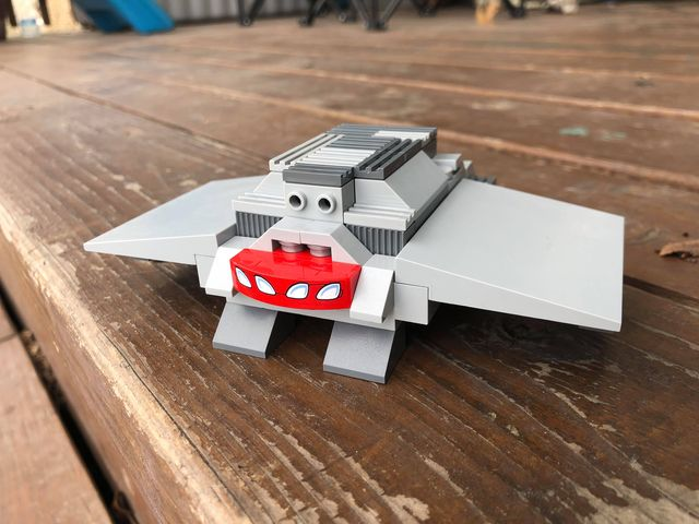 Lego armadillo that looks like an airplane. Body and armour are in light and dark greys, with wide flat wings sticking out to the side. The mouth is a red piece with painted-on almost-human teeth.