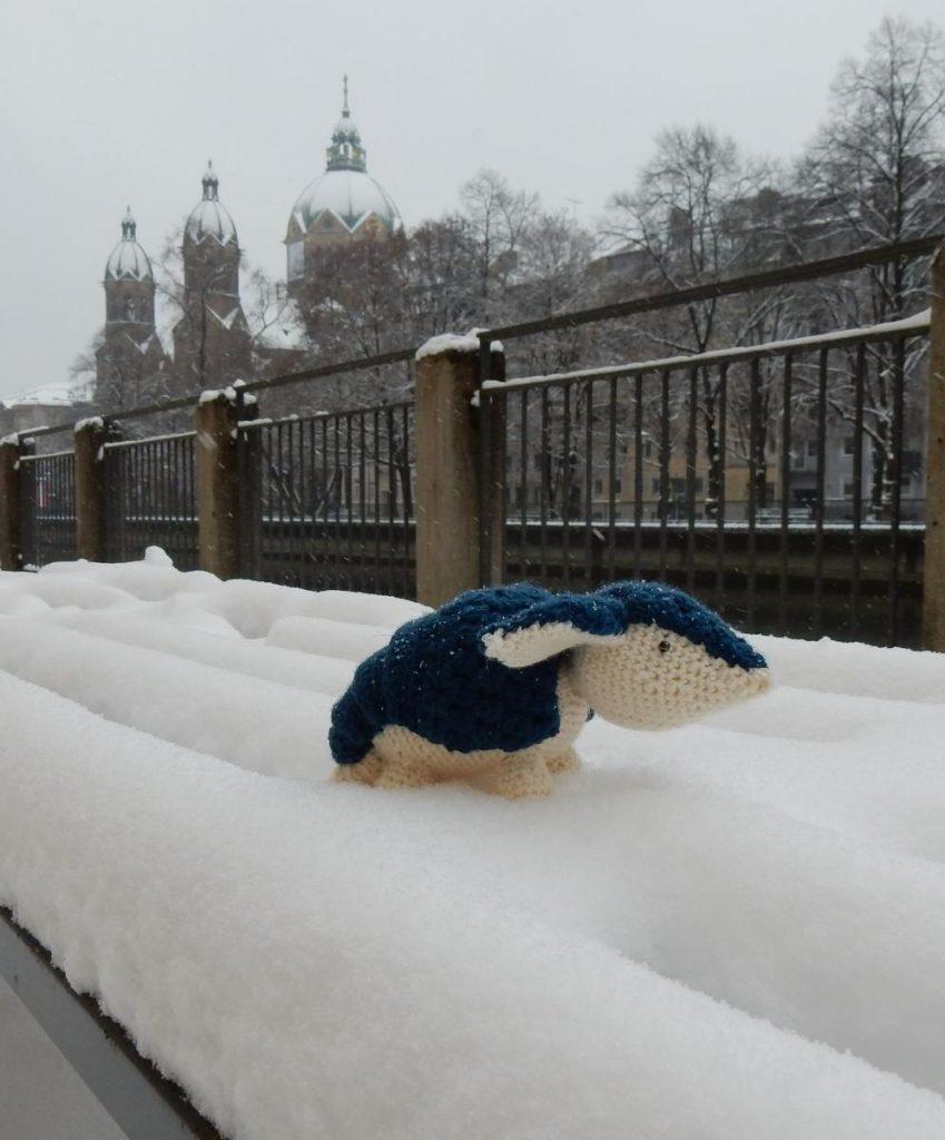 Berta the crochet armadillo sitting on a snowed-in bench in Munich.
