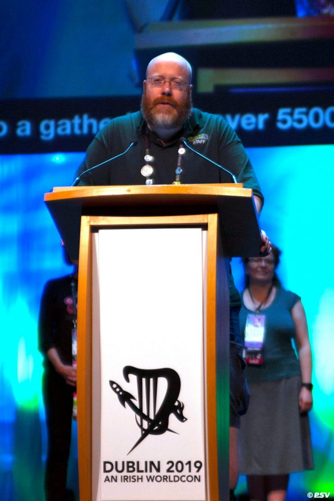 Brian Nisbet standing in front of a lectern with an inscription that reads 'Dublin 2019 An Irish Worldcon'