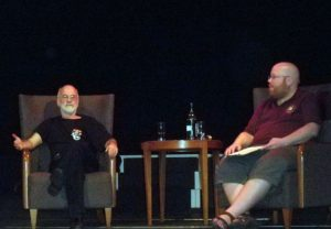 Brian Nisbet sitting across a small table from writer Terry Pratchett