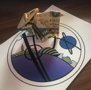 Origami armadillo made from a dollar bill sitting on top of a Glasgow in 2024 logo sticker