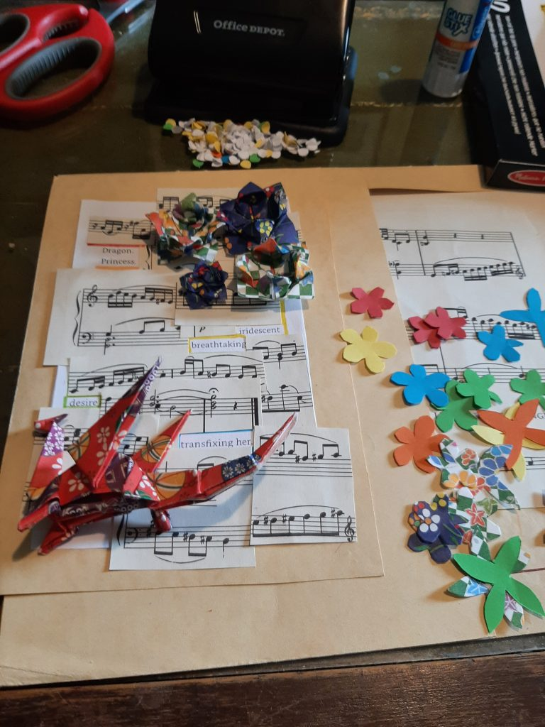 The image shows component pieces of the sheet music and poetry, origami flowers and dragon, and small paper flowers in multiple colours.