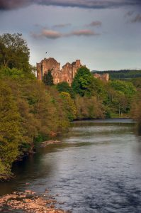 photograph of an imposing castle on a forested riverbank, lit by the setting sun
