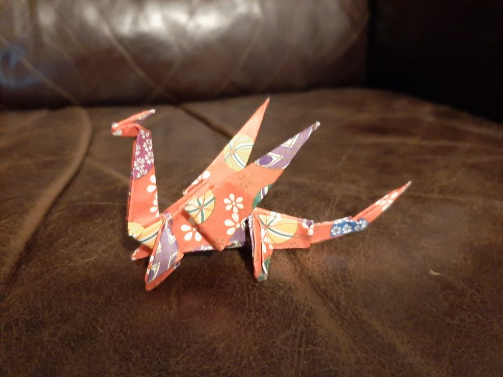 Image shows an origami dragon made out of orange paper with colourful patterns on it in yellow, white and purple