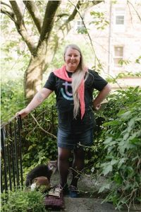 Image shows: Elaine standing in the centre of greenery, her hand is resting on an iron rail. She is wearing a dark tshirt, a denim skirt, and a bright pink scarf. Her long hair is over her right shoulder and she is smiling.