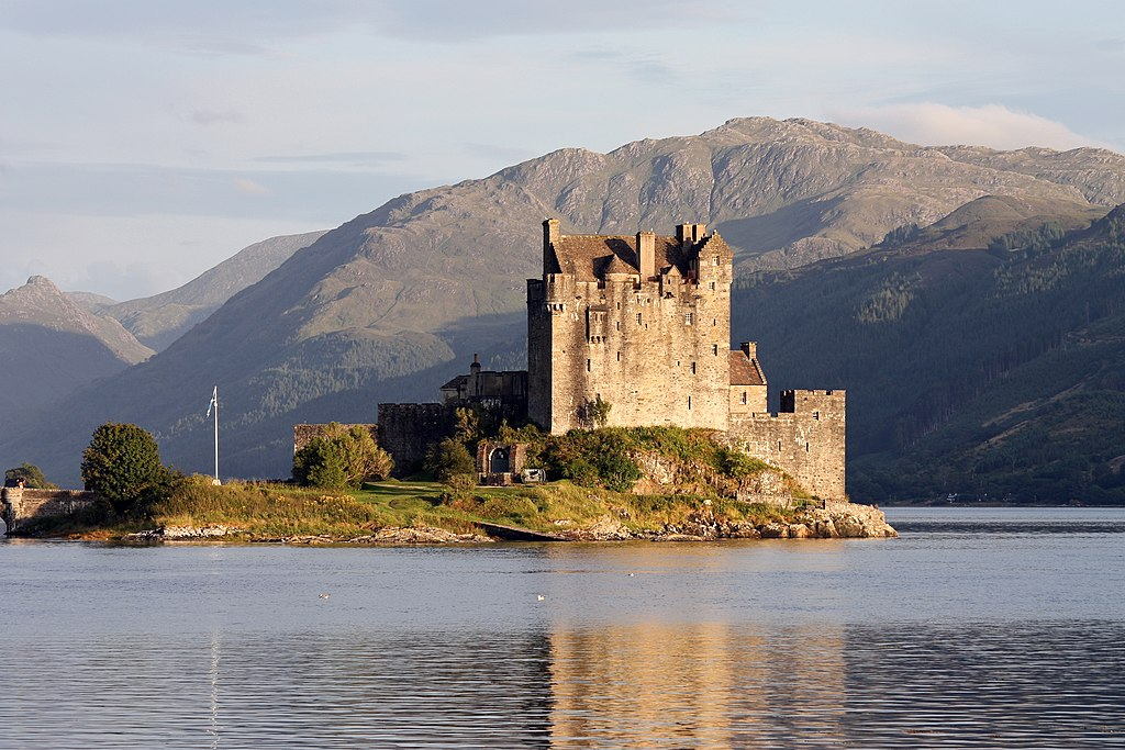 photograph of a castle on a small island on a lake against a mountainous backdrop