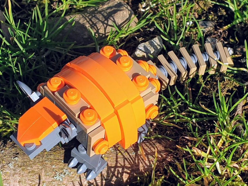 A lego armadillo sitting in the grass. The body is grey and light brown, the armour a bright orange.