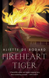 Image shows the cover of Aliette De Bodard's Fireheart Tiger. The cover's central image is a woman in a beautiful red and gold robe - reminiscent of a fire. In her hands there is a tea cup out of which a glorious set of flames blazes. Only the chin, mouth and nose of the woman's face is visible, along with the edges of a gold headdress. Faded into the right sleeve of the role there is an overlaid image of siheyuan style buildings. Behind the woman is the fade image of 4 pillars.