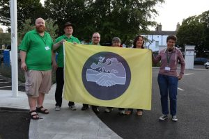 A group of people holding up a yellow flag with a grey circle in the middle. In the centre of the circle there is an image of two clasped hands under the map of Europe.