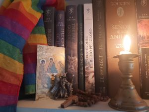 The image shows the close up of a bookshelf. On the left hand side there is a rainbow striped flag draped over some of the books. Next to the flag is postcard with a gilt backgrounded, in the foreground 3 figures sit in robes heads slightly bowed each figure has aureola surrounding their heads. It looks to be a replica of a medieval piece of religious art. Next to that is a a small pertwer statue of a wizard in long robes, a pointed hat, one hand holding a staff, the other is outstretched. The next item on the shelf is a set of wooden rosary beads piled on top of themselves with the simple cross facing outwards. lastly at the far right of the image is a low burning white candle in a pottery holder. There is wax that has spilled on the bottom of the candle holder. The candle is casting a soft light onto the books in the background. These bookes are not all visible but they are different editions of J.R.R Tolkien's work translated into Spanish. Of the books that can be identified there is a copy of The Hobbit and The Silmarillion.