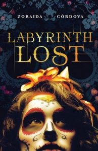 The image shows the cover of Zaoraid Cordova's novel 'Labyrinth Lost'. The lower half of coveris taken up with an upturned face which is covered in make up to resemble a dia de lost murtos skull. They have an orange flower in their hair .