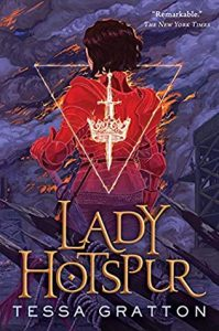 The image shows the cover of Tessa Gratton's 'Lady Hotspur'. The background of the image is a grey purple smoke filled sky. In the centre of the image a figure stands, back toward us, in red armour, orange flames edge it in places. Overlaying this is an inverted triangle in the centre of whitch is a sword through the centre of an ornate crown. These are all in white flame. The title 'Lady Hotspur' is in golden lettering along the bottom of the cover, behind witch sharpened pikes point towards the figure.
