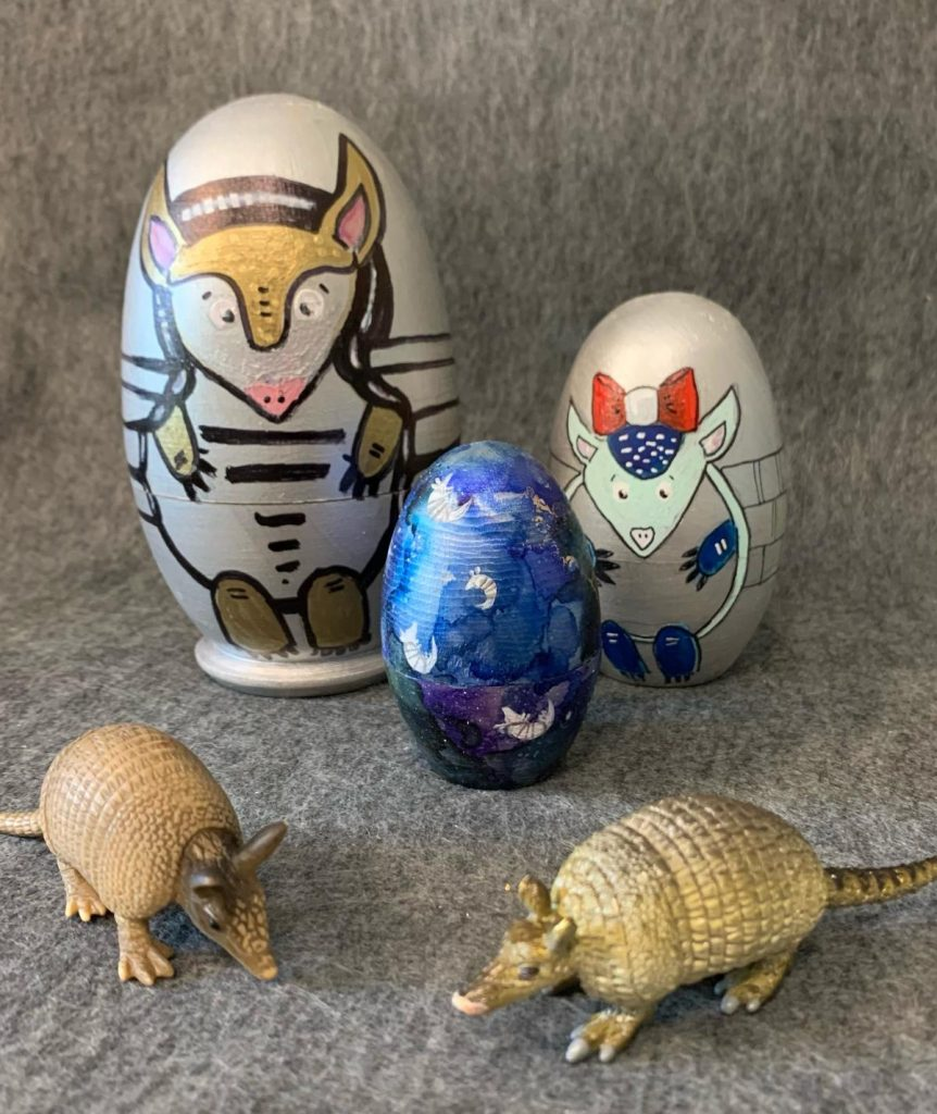 Set of three nesting dolls, painted with armadillos. The biggest on the left in silver with gold details, the middle size on the right with a silver background, light teal head and blue arms and legs. The head is crowned by a big red and white bow. In the middle in front is the smallest doll with many small white armadillos floating on a mottled blue background.