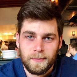 Headshot of Luke Shelton's face smiling , he is wearing a blue shirt.