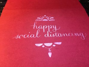 """A red banner that reads """"happy social distancing"""""""