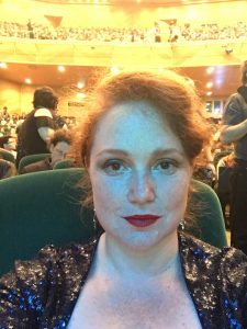 Marguerite at the Hugos in Dublin 2019. A smiling woman with auburn hair and red lipstick in a glittering black top, looking made up and ready for an event.