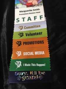 Marguerite's Staff Badge from Dublin Worldcon in 2019 featuring a series of ribbons showing her many roles and active involvement.