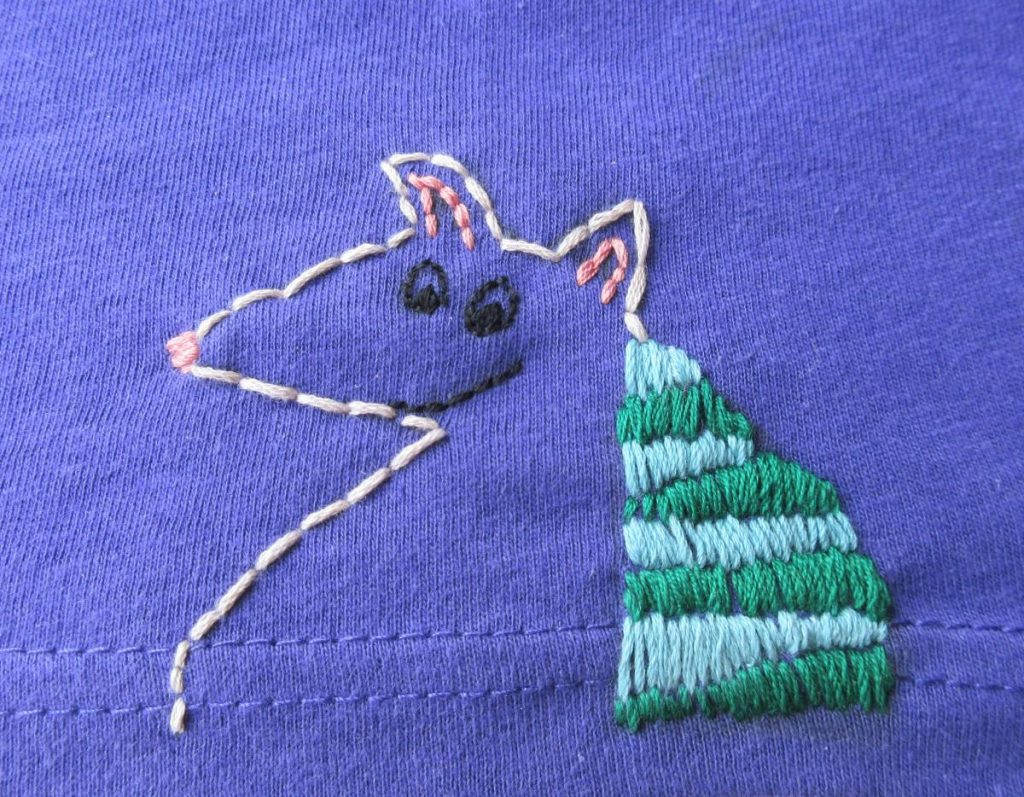 Stylized armadillo embroidered on the seam line of a purple Glasgow in 2024 tshirt. The body is outlined in cream, and the armour has alternating green and light blue stripes.