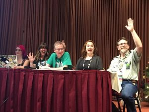 An image taken at a panel at a con. Five people sat at a table, waving at the camera and looking very excited to be there
