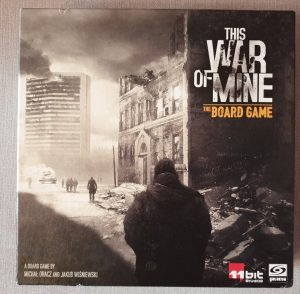 The front of 'This War of Mine' box, with the title in large grey letters at the top right. The image of a war-torn cityscape covers most of the box, with a shadowed figure in the foreground, looking towards rubble, a dilapidated building, and - in the background - a smoking skyscraper.