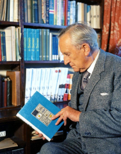 JRR Tolkien holding a blue book in front of book cases. Image credit The Tolkien Society