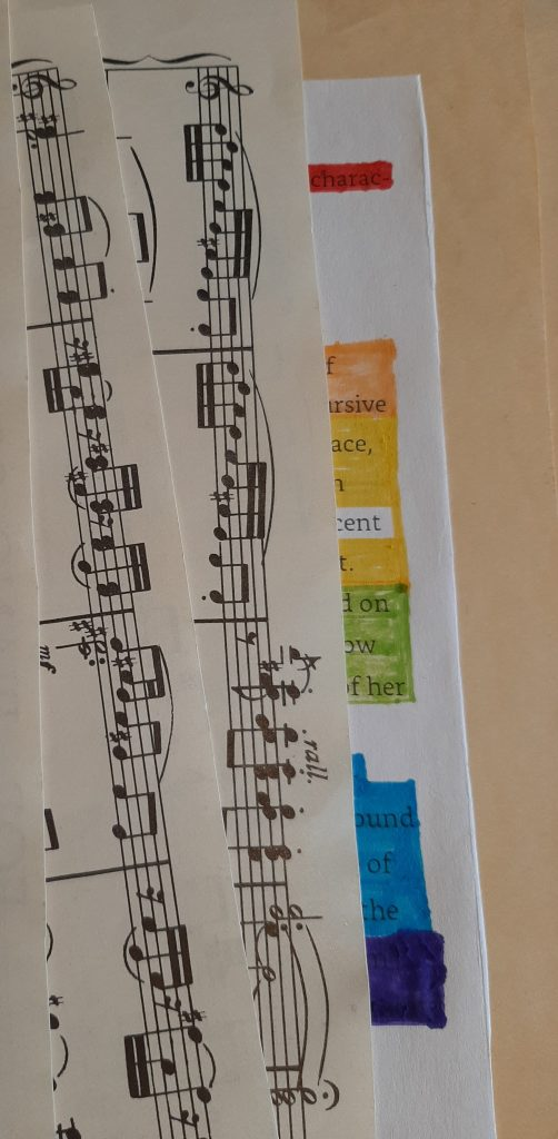 The image shows sheet music over the edge of a text document where large sections of the text have been obscured using a rainbow of coloured pens.