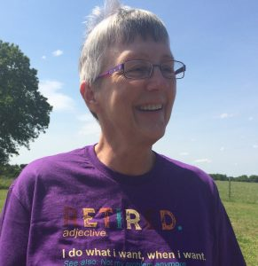 """The image shows a head and shoulders shot of Robin Reid. She has cropped short grey hair that is being blown up by a breeze and is smiling. She is wearing purple framed regtangular glasses and a purple tshirt. On the Tshirt there is the following text in luticoloured lettering """"RETIRED. adjective. I do what i wasnt, when I want."""" The remainder of the text is cut off. Behind her on the left is the edge of a large tree, a bright blue sky and green feilds."""