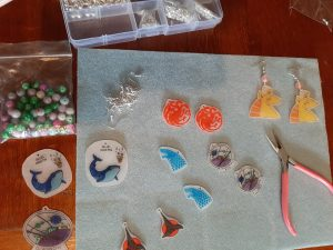 Work space with the finished pendants, earrings and jewellery supplies: different types of beads, earring hooks, and round-nose pliers.