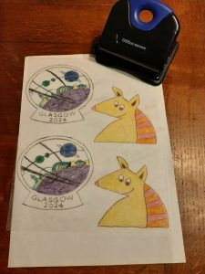 Images transferred to the Shrinky Dinks plastic and coloured in. On the top right there's a hole punch.