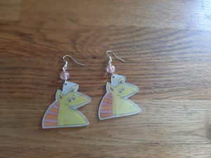 A pair of finished armadillo earrings, coloured in with a pink bead between the armadillo and the earring claw.