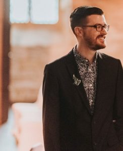 The images shows an upperbody porttrait shot of Taylor Driggers. He is wearing a charcoal grey suit, a grey and white patterned shirt. on the lapel of the suit is a the leaf pin given to hobbits in Lord of the Rings. He is looking to the right and smiling to something off camera. He is wearing rectangular glasses, and his brown beard is short and tidy. His brown hair is shorter on the sides, longer on the top and swept from right to left.