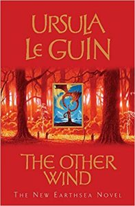 The image shows the cover of Ursula Le Guin's novel 'The Other Wind'. The cover has a red colour palate. In the centre third of the cover there is a sparse forrest scence of the trunks of trees rendered in gold and brown. In the very centre of that - positioned between two tree trunks - is a regtanfular frame of a blue sky, a mountain tower and a red dragon.