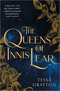 The image shows the cover of Tessa Gratton's 'Queens of Innis Lear'. The title is in the centre of the cover in gold writing. Golden brzone leaves trail up the bottom left and top right of the cover. The background is a dark blue star filled sky.
