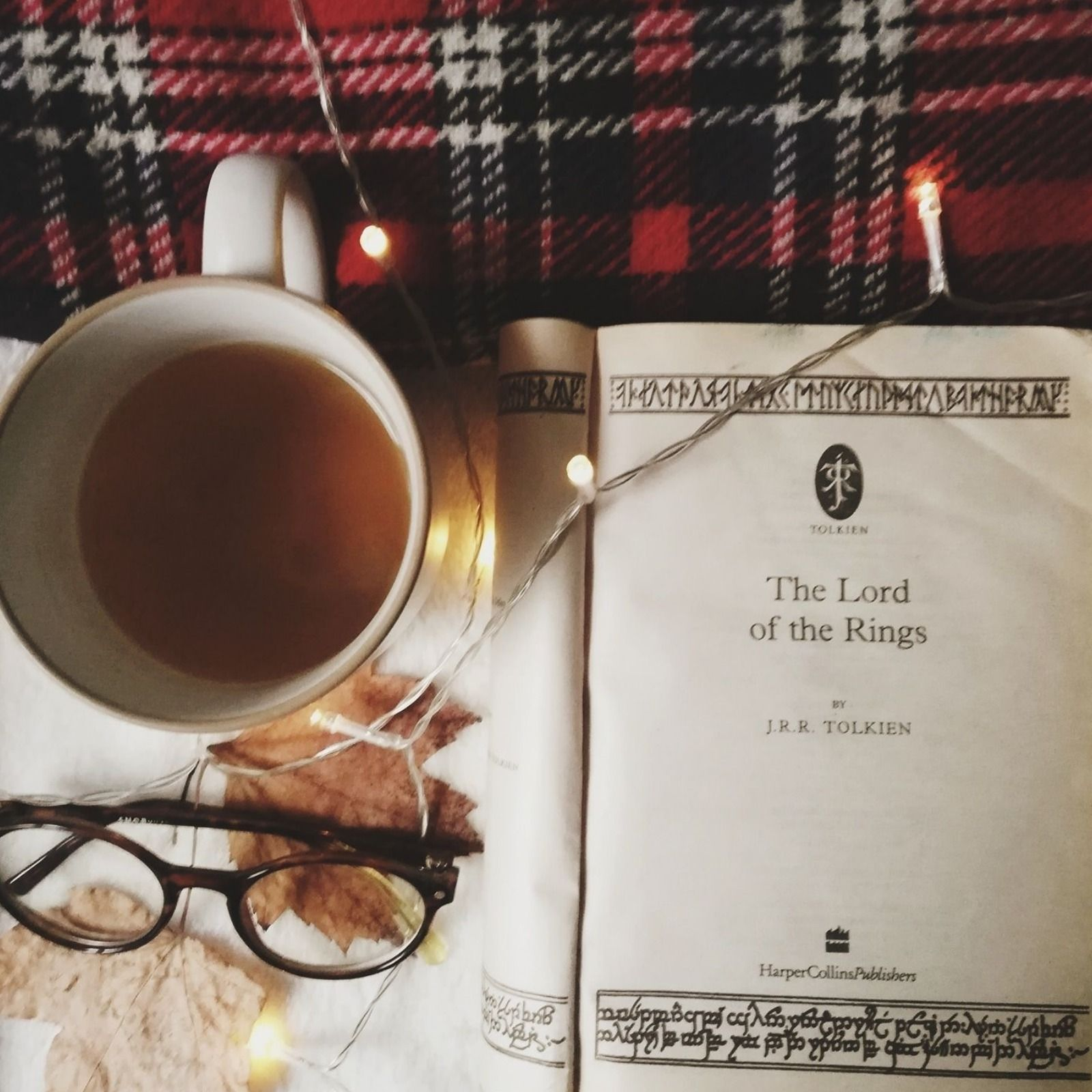 A copy of the Lord of the Rings open at the title page, surrounded by fairy lights, a mug of tea, autumn leaves, and a pair of glasses