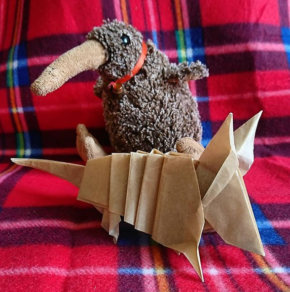 Origami armadillo made from thin brown paper, shown in front of a plushie.