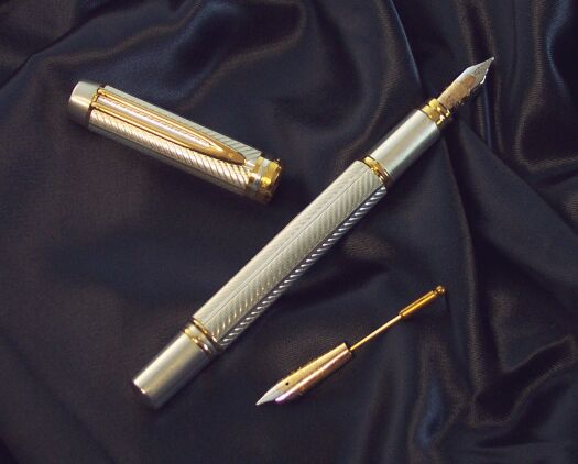 Image of the parts of a silver and bronze fountain pen sat on a navy-coloured cloth. In the middle is the pen itself, to its left is the cap, and to its lower right is a secondary bronze nib.
