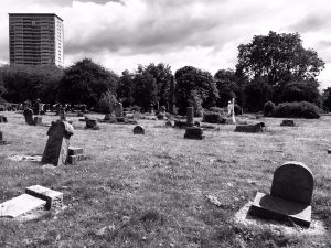 Landscape shot in black and white of the Southern Necropolis in Glasgow - tower blocks in the distance, gravestones in the fore view