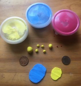 Materials for polymer clay armadillo: three tubs of clay in yellow, blue and pink at the top, several balls of yellow and pink already formed below, and two pieces rolled out flat in blue and yellow at the bottom. Left and right: two pennies for scale.