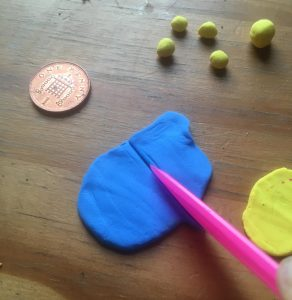 Blue sheet of clay being cut by a knife-like tool, with a penny coin and several balls of yellow clay in the background