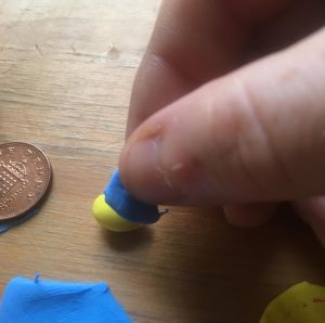 A small piece of the blue sheet of polymer clay is being wrapped around the yellow head form.