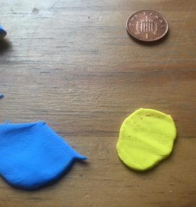 Remaining pieces of blue and yellow sheets of clay, slightly bigger than a penny. Penny for scale.
