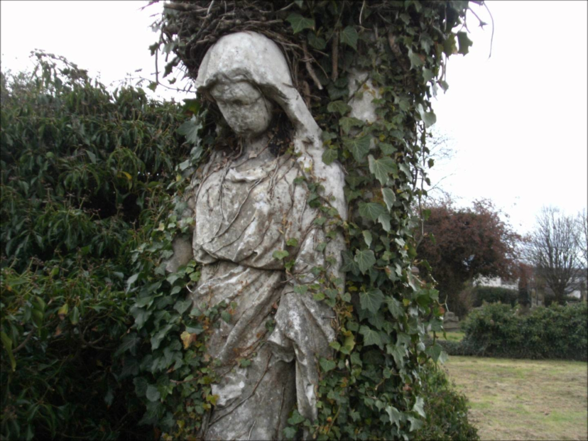 Image from Southern Necropolis Glasgow of hooded female statue shrouded in ivy